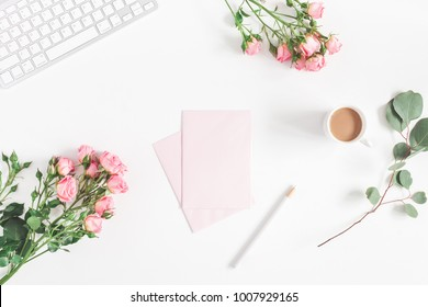 Office desk with computer, rose flowers, eucalyptus branch, pink paper blank. Flat lay, top view, copy space.