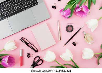 Office desk with computer, tulip flowers, cosmetics, glasses, diary and pen on pink background. Flat lay. Top view.