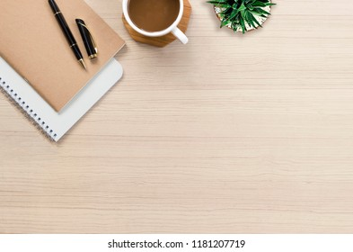 Office desk flat lay with hot coffee, notebook and plant on top view and copy space. Business desk minimal style concept.