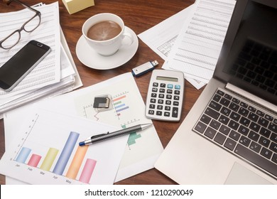 office desk full with documents, glasses, laptop, and coffee, concept for business and finance, selected focus, narrow depth of field