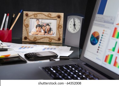 Office desk full of stuff: laptop, clock, document, family picture and other things.