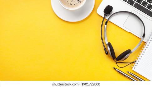 Schreibtisch mit Kopfhörer, Kaffee und Laptop. Remote-Büro und Arbeit von zu Hause Konzept. Draufsicht, flacher Laibe mit Kopienraum