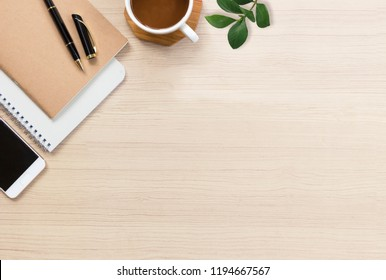 Office desk with hot coffee, plant, vintage eyeglasses, notebook and smartphone on top view. Flat lay of Business desk minimal style concept with copy space.