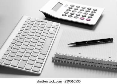 Office desk with keyboard, ballpoint, spiral notebook and calculator with shallow depth of field