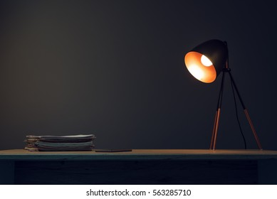 Office desk with lamp, mobile phone and paperwork stack