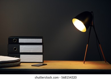 Office desk with lamp, ring binders and mobile phone