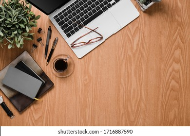 Office desk with laptop, agenda, glasses and clips in a woody background