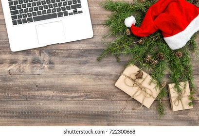 Office desk laptop with Christmas decoration red hat and gifts. Top view Flat lay