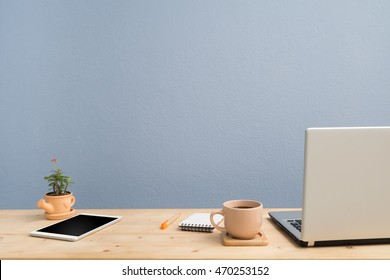 Office desk with laptop, Note paper, Euphorbia milii flower on terracotta flowerpot and blank screen tablet. View from front wood table.