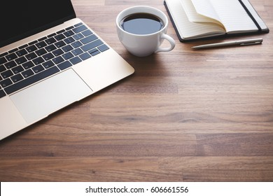 Office desk with laptop and notebook and coffee cup