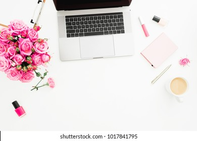 Office desk with laptop, pink roses bouquet, coffee mug, pink diary on white background. Flat lay. Top view. Fashion or freelance concept with copy space