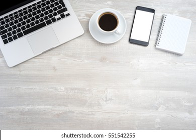 Office desk with laptop, smartphone, cup of coffee. Top view with copy space.