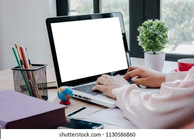 Office desk mockup concept.Mockup modern desktop with woman hand using blank screen laptop computer and a lot of things on desk.