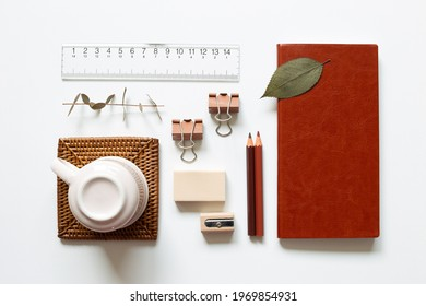 Office desk. Notebook, colored pencel, pencil sharpener, eraser, clip, cup, ruler on white background. top view, copy space