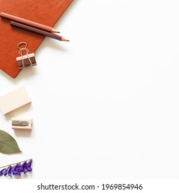 Office desk. Notebook, colored pencel, clip, eraser, pencil sharpener on white background. top view, copy space