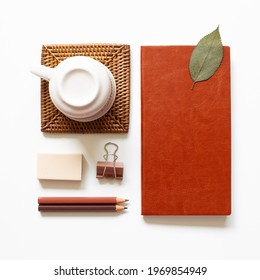 Office desk. Notebook, colored pencel, clip, eraser, cup on white background. top view, copy space