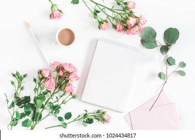 Office desk with notebook, rose flowers, eucalyptus branch, pink paper blank. Flat lay, top view, copy space.