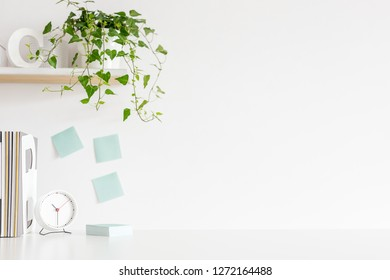 Office desk with notebooks, supplies, alarm clock, notebooks and white wall for mock up or copy space.