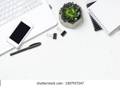 Office desk with notepad, coffee cup, succulent and pen on white background. Top view with copy space