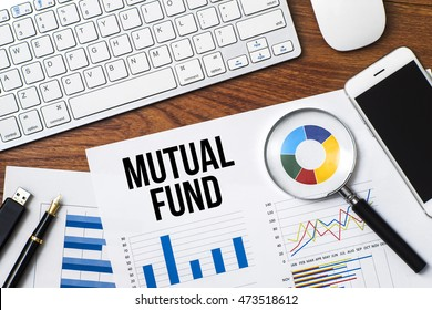 Office desk with a paper of charts written MUTUAL FUND with keyboard, mouse, pen, magnifying glass, smartphone and a thumb drive - Business concept top view with copy space