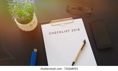 Office desk with a paper written checklist 2018 with pen, glass, smartphone and a lighter