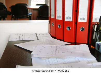 office desk with red folders and various documents