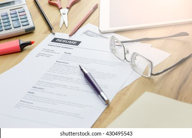 Office desk with resume information, highlighter, calculator, Scissors, pencil, pen and glasses.