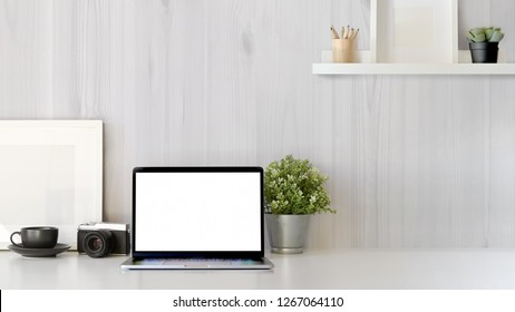 Office desk scenery with mockup blank screen laptop computer. Workspace minimal