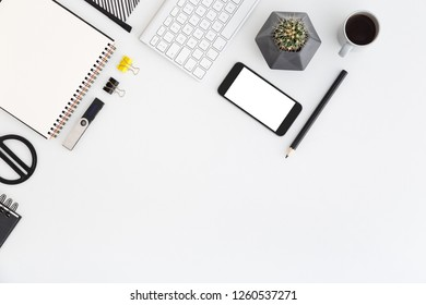 Office desk with smartphone, cup of coffee, cactus and office supplies on a white background. View from above.