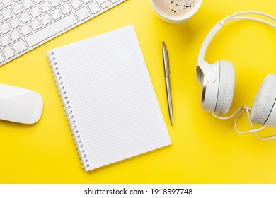 Schreibtisch mit Vorräten, Kopfhörern und leerem Notizblock auf Gelb. Konzept der Kreativität und Inspiration. Draufsicht, flacher Laibe mit Kopienraum