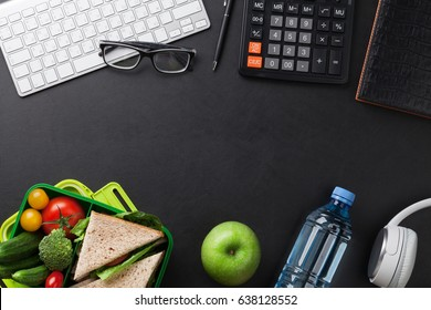Office desk with supplies and lunch box with vegetables and sandwich. Top view with space for your text