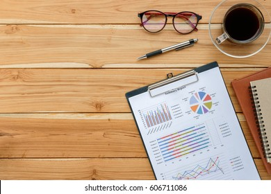 Office desk table with analysis chart or graph, pen, eyeglass and cup of coffee. Top view with copy space.Working desk table concept.