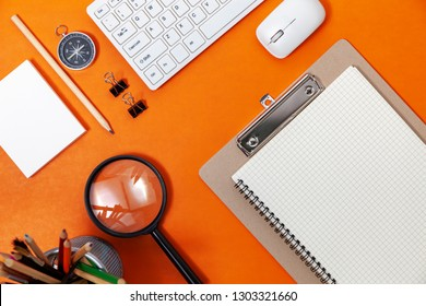 Office desk table of Business workplace and business objects of keyboard,mouse,white paper,notebook,pencil,compass on orange background..