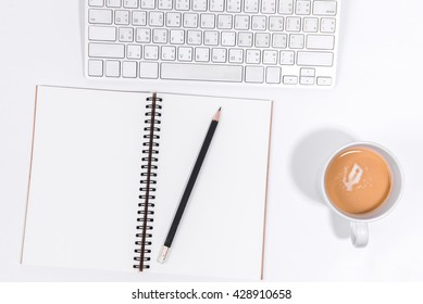 Office desk table with computer, Blank notebook with black pencil and coffee cup. Top view with copy space