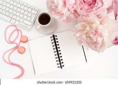 Office desk table with computer, cup of coffee and peony flowers. White wooden background.