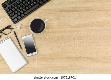 Office desk table with computer keyboard,coffee,glasses and  blank notebook. Top view with copy space on wooden background.