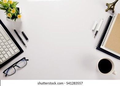 Office desk table with keyboard, notebook, pen, cup of coffee and flower. Top view with copy space (selective focus)