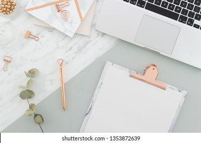 Office desk table with laptop, clipboard, rose gold pen, clips and supplies, pretty eucalyptus branches on marble gray background. Top view with copy space