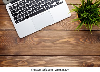Office desk table with laptop computer and flower. Top view with copy space