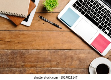 Office desk table with laptop,pen,tablet,notebook and cup of coffee.Flat lay photo.Top view with copy space.Working desk table concept.
