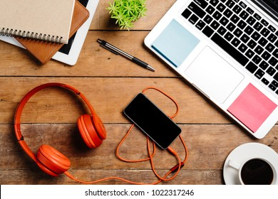Office desk table with laptop,smart phone,pen,headphone,notebook and cup of coffee.Flat lay photo.Top view with copy space.Office supplies and gadgets on desk table.Working desk table