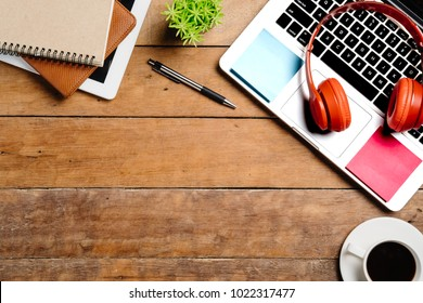 Office desk table with laptop,smart phone,pen,headphone,tablet,notebook and cup of coffee.Flat lay photo.Top view with copy space.Working desk table concept.