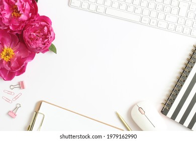 Office desk table with notebook, computer, pen, paper clips and  pink peony flowers. Space for text. Top view.