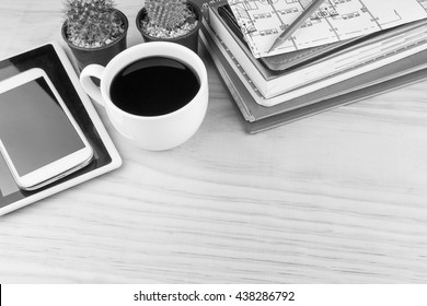 Office desk table with notebooks,glasses, smart phone and a cactus with cup of coffee.Top view with copy space. Business concept.black and white tone