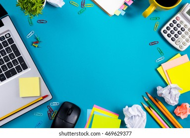Office desk table with set of colorful supplies, white blank note pad, cup, pen, pc, crumpled paper, flower on blue background. Top view and copy space for text
