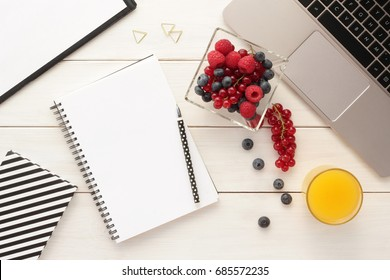 Office desk table with spiral notebook,  computer, berries in a bowl  and orange juice on white wooden table.  Ideas, notes, plan writing, working break,  diet plan concept. Top view, flat lay.