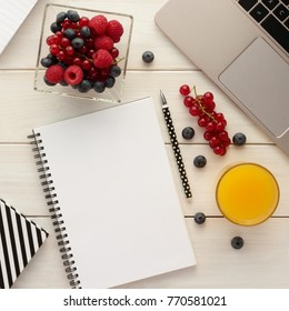 Office desk table with spiral notebook,  computer, berries in a bowl  and orange juice. White wooden background. Ideas, notes, plan writing, working break,  diet plan concept. Top view, flat lay.