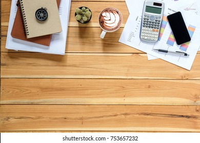 Office desk table with stack of business report paper file, calculator,smart phone,cup of coffee and financial report.Top view with copy space.Working desk table concept.