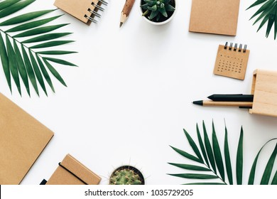 Office desk table with stationery set, supplies and palm leaves. Top view with copy space, creative flat lay.