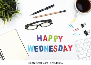 Office desk table with supply, pen, pencil, notebook, computer, eye glasses, sticky note, cup of coffee and happy wednesday word on white background